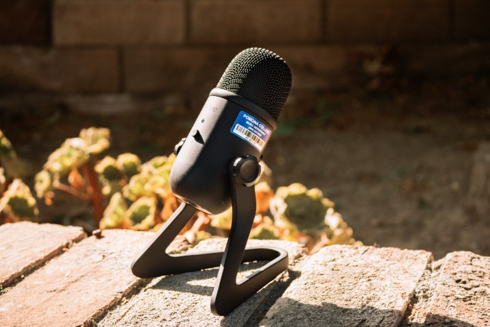 """A black desktop mic with a stand. There is a sticker on the mic that reads """"Pomona College."""""""