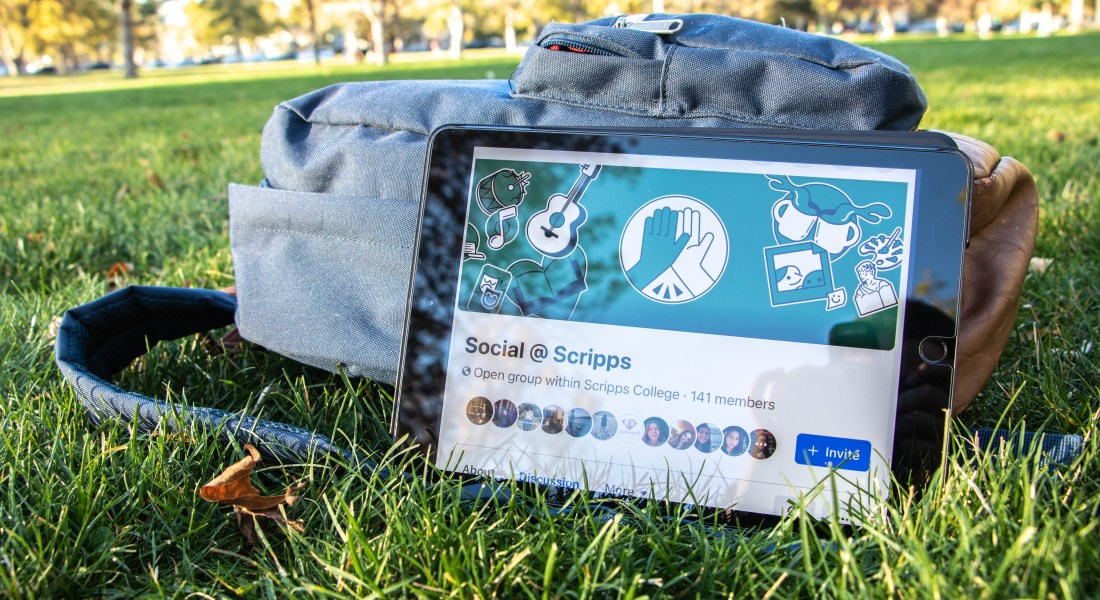 "An iPad leans up against a backpack on a grass lawn. The iPad is open to a Facebook page that reads ""Social @ Scripps."""