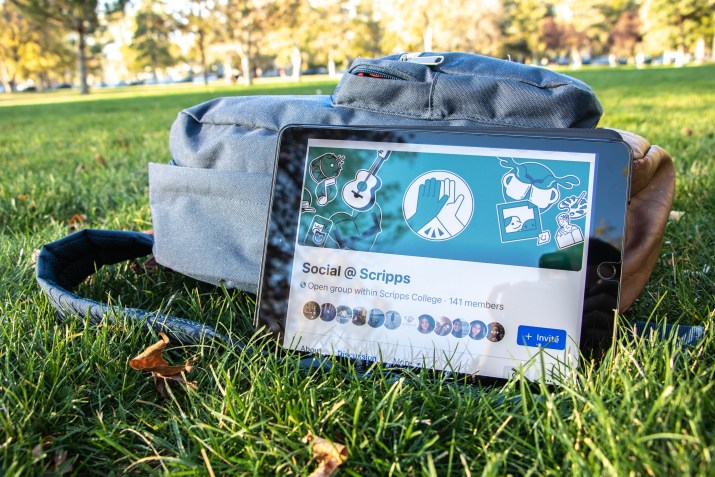 """An iPad leans up against a backpack on a grass lawn. The iPad is open to a Facebook page that reads """"Social @ Scripps."""""""