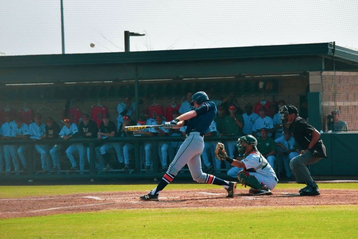 A baseball player swings a bat in front of a crowded dugout