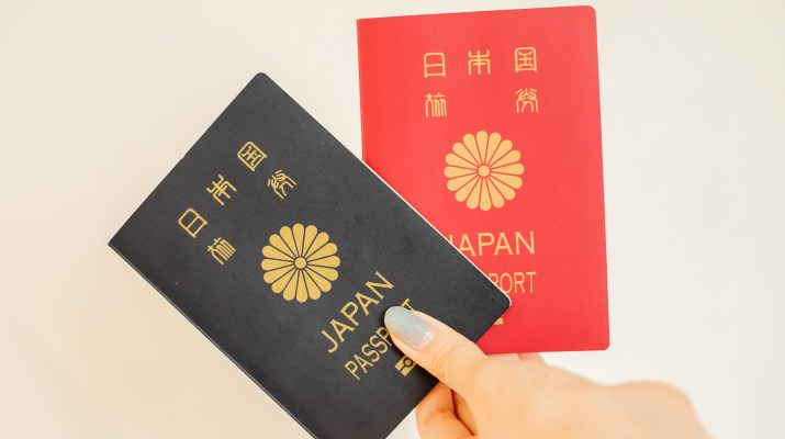 A person holds one red and one blue Japanese passport.