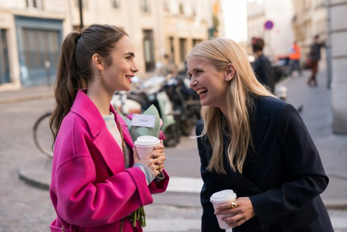 Two women holding white coffee cups laugh on the street
