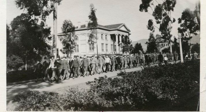 Multiple soldiers wearing masks and hats march through campus.