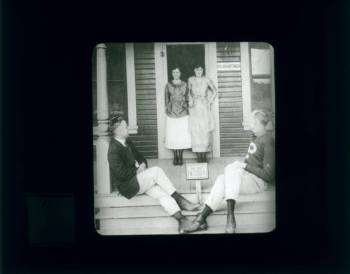 Two men sit on a porch in front of two women.