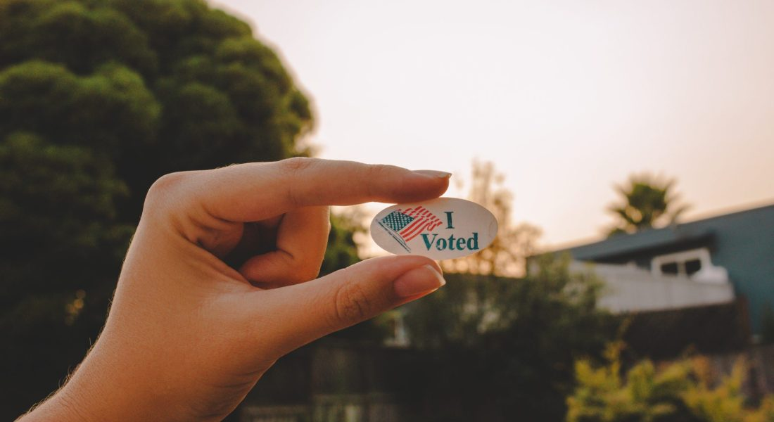 "A hand holds up an ""I Voted"" sticker outdoors."