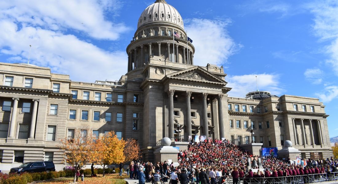 During Red Ribbon Week, students across the nation participate in marches and events to bring awareness to drug usage in youth. (Courtesy: Tamanoeconomico via Wikimedia Commons) A group of people wearing red stand on the steps of a capitol building.