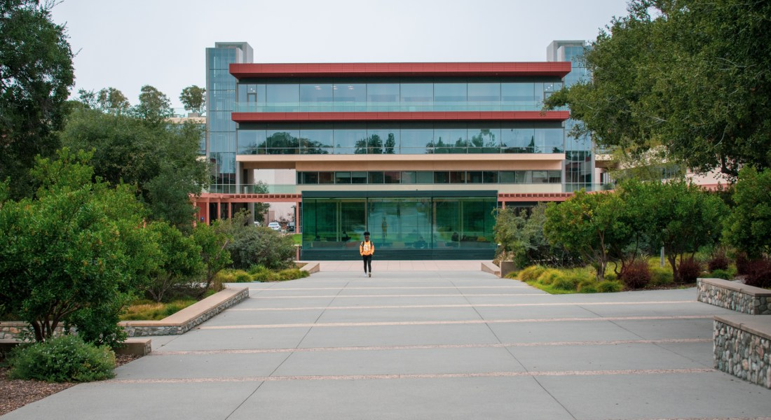 A glass building stands between green trees on the side of a concrete path, a student walks