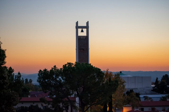 A large bell tower and clock overlook the sunset.