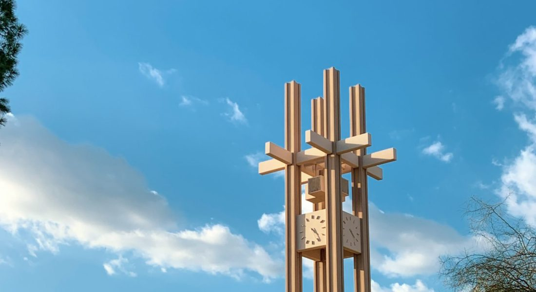 A clock tower with a blue sky and clouds and trees