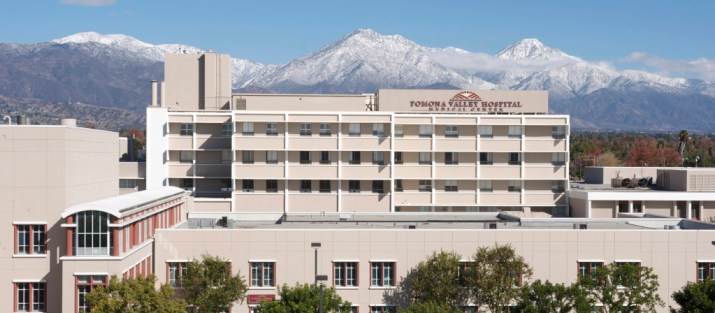 The Pomona Valley Medical Center Hospital stands in front of snowy mountain peaks.