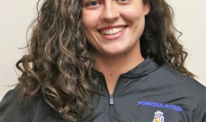 """A woman with brown curly hair wears a black jacket with a log which reads """"Pomona-Pitzer Football""""."""