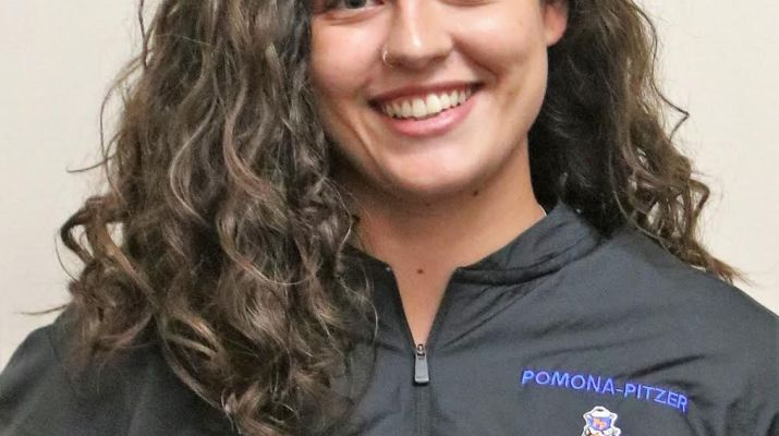 "A woman with brown curly hair wears a black jacket with a log which reads ""Pomona-Pitzer Football""."