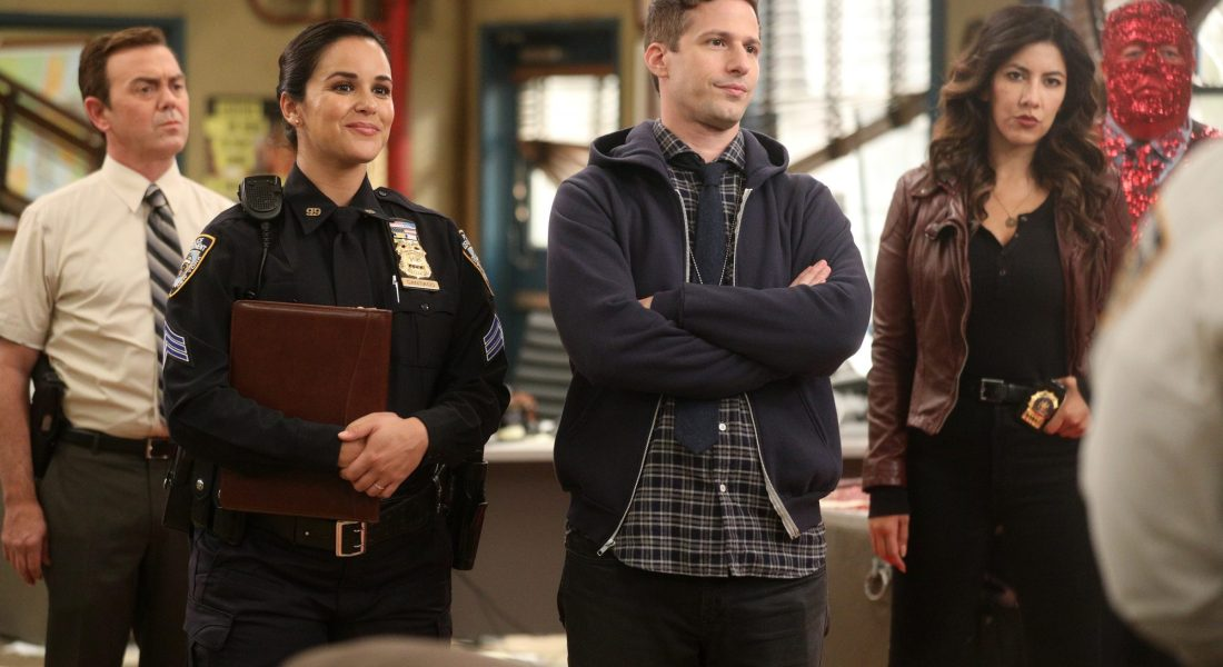 Three characters from the cop show Brooklyn Nine-Nine stand together in a police station.