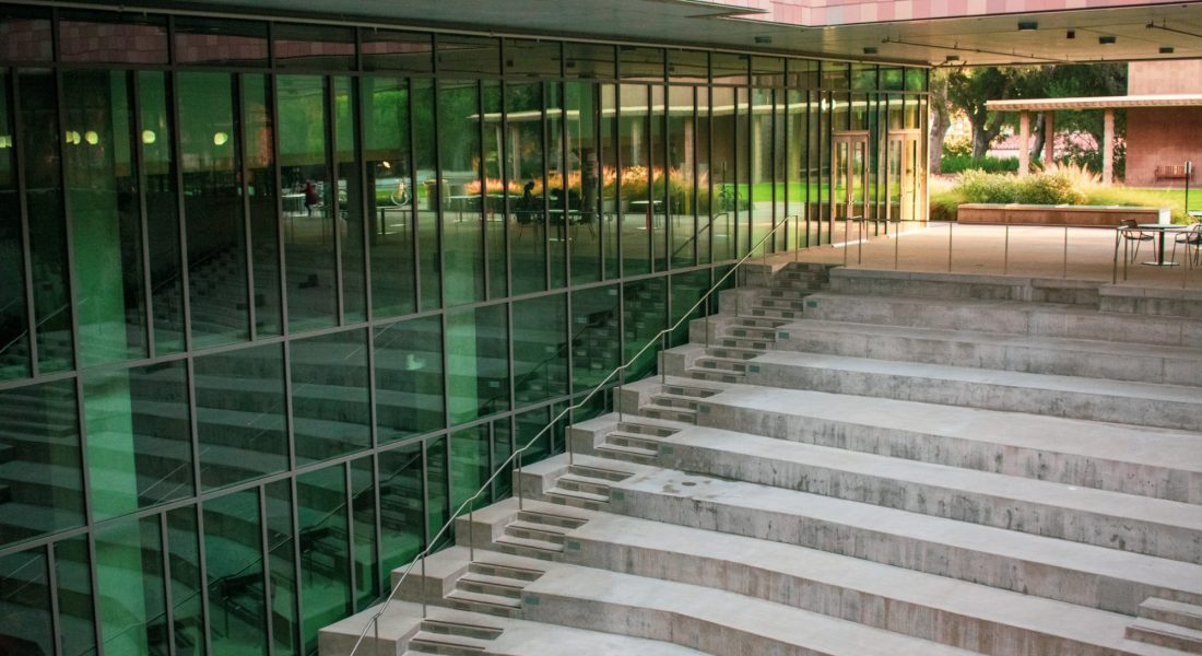 A set of concrete stairs next to a glass building.