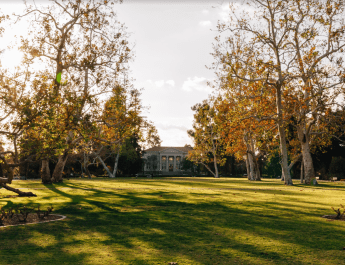 A green lawn is surrounded by trees with yellow leaves, a white building is in the center.