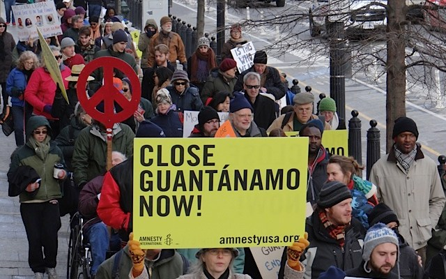 A large crowd of protestors are gathered in front of the White House, holding various signs that rally for the closure of Guantanamo Bay.