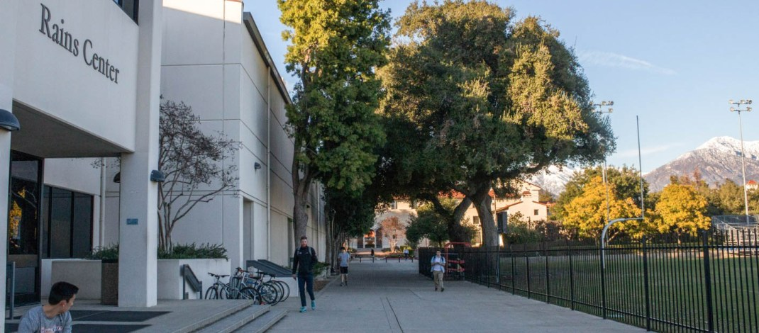 """Students walk on a sidewalk surrounded by a football field and a building called the """"Rains Center""""."""