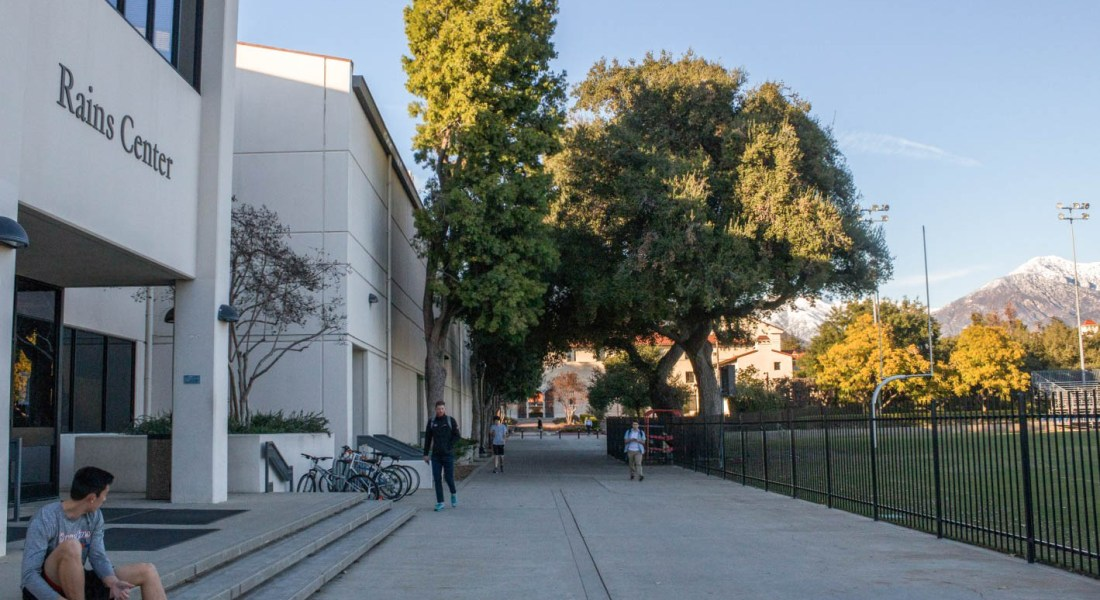 "Students walk on a sidewalk surrounded by a football field and a building called the ""Rains Center""."