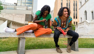 A man wearing a colorful shirt sits next to a woman wearing a green shirt and orange pants. Both hold water bottles.