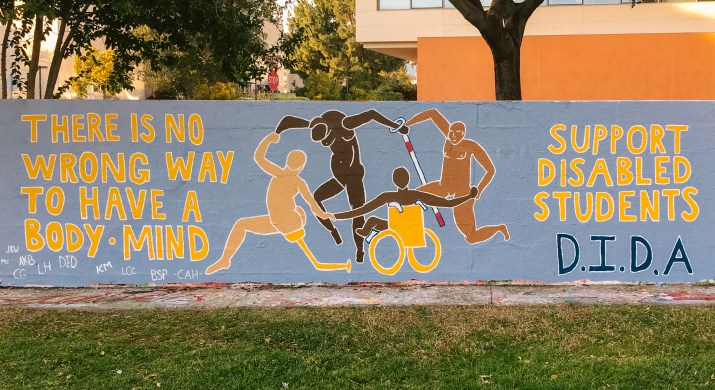 """A mural reads """"There is no wrong way to have a body • mind. Support disabled students D.I.D.A."""""""