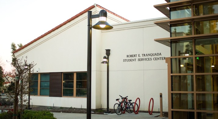"""A white building with a red roof has a sign reading """"Robert E. Tranquada/Student Services Center""""."""