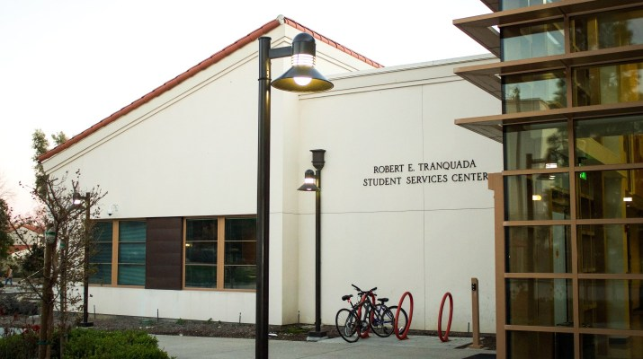"A white building with a red roof has a sign reading ""Robert E. Tranquada/Student Services Center""."