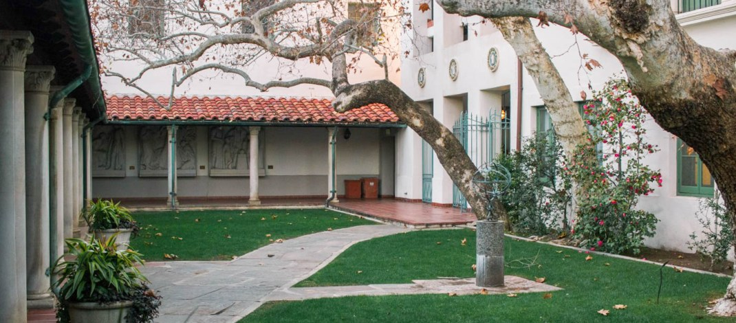 A green courtyard is surrounded by white buildings with red tiles.