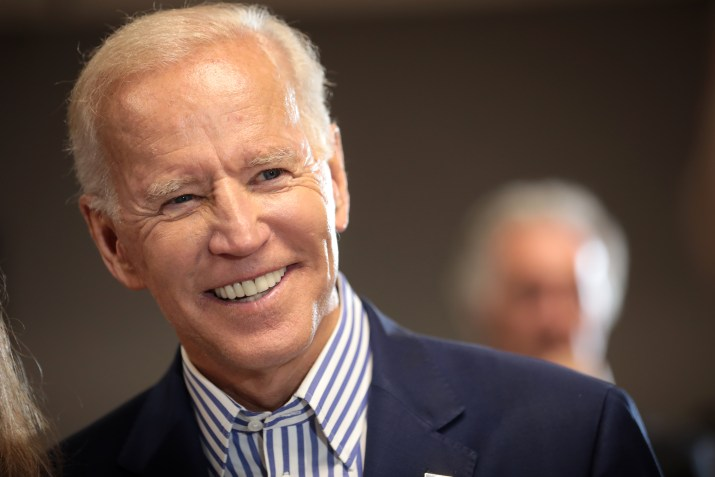 An older man wearing a blue and white striped shirt and clue blazer smiles at something off camera.