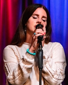 A brown-haired woman wearing a pink sweater, a teal bracelet and teal ring closes her eyes and sings into a microphone in front of a blue and red curtain.