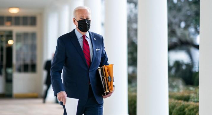 Joe Biden is wearing a blue suit and a black mask.