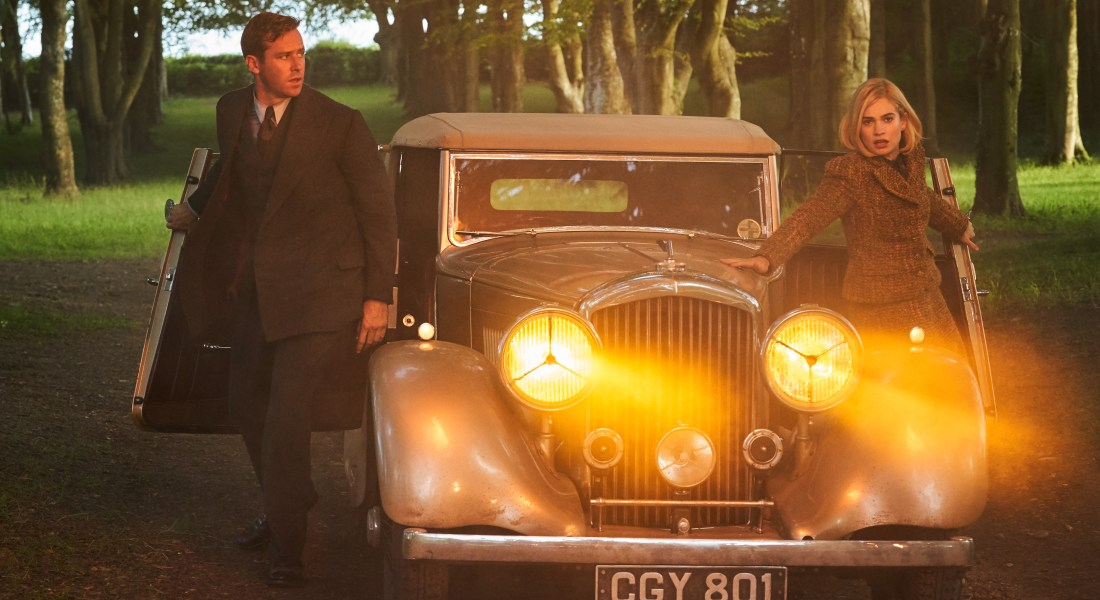A man and woman leap out of an old car whose large headlights shine yellow.