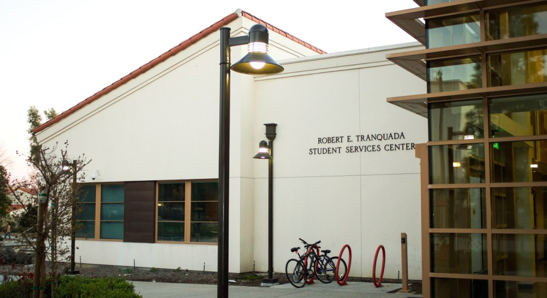 "A white building with a red tile roof has a sign reading ""Robert E. Tranquada, Student Services Center""."