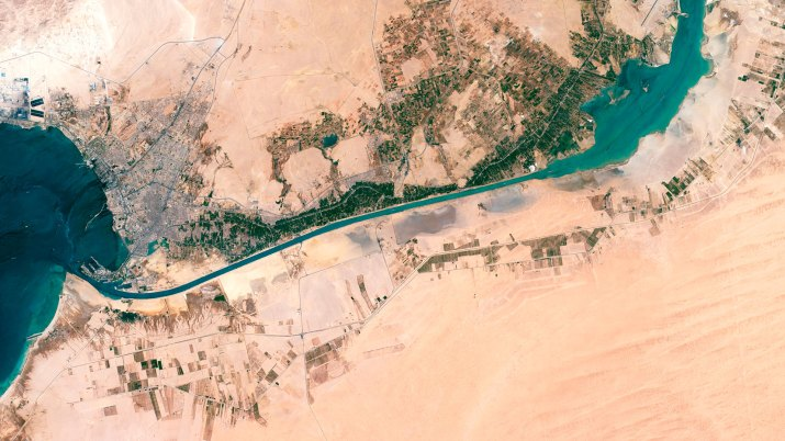 An aerial view of a long, skinny, blue canal surrounded by desert.