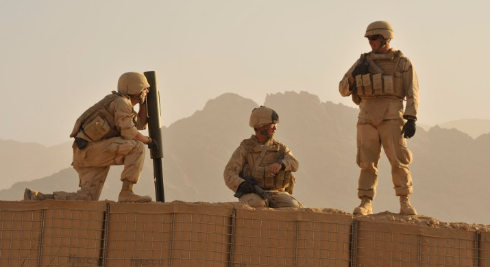 Three solders stand on a wall in front of a hazy mountain.