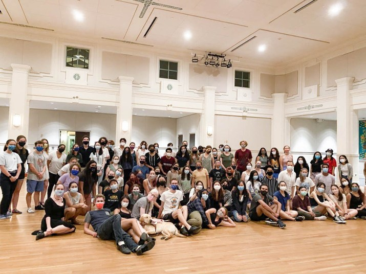 Around 100 people pose for a photo in a ballroom.