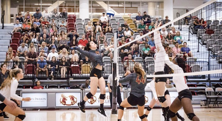 Two women's volleyball teams play on a court.