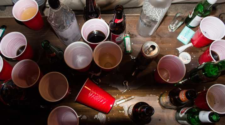 A table is strewn with red cups and bottles of alcohol.