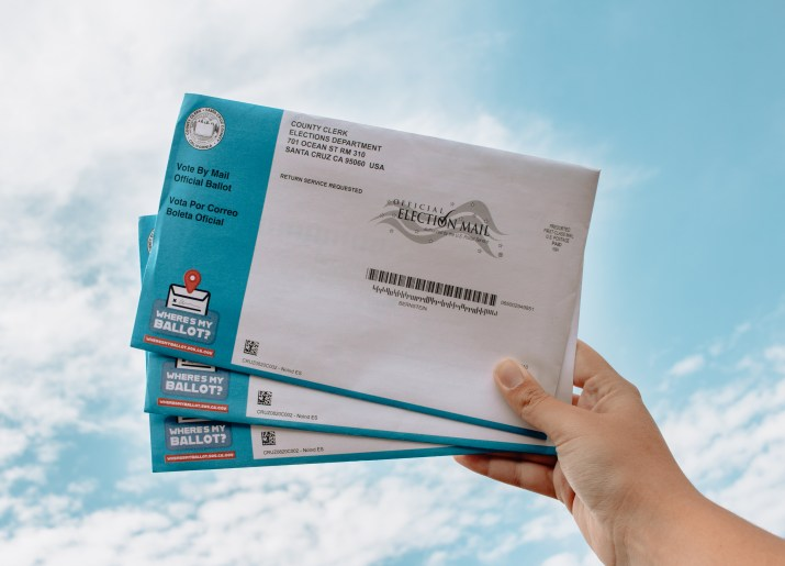 A hand holds up ballots under the blue sky.