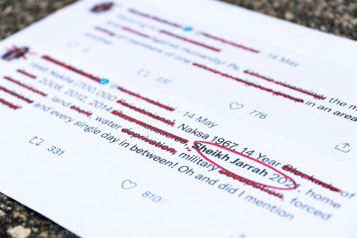 """Words such as """"Gaza massacres,"""" """"land theft,"""" """"water deprivation"""" are crossed out in red marker."""