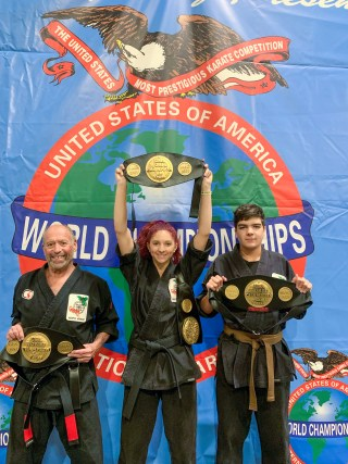 Danika Petit, dressed in martial arts robes, holds the champion belt up high.