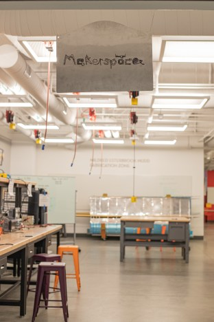 A room with machinery can be seen behind a sign that reads Makerspace.