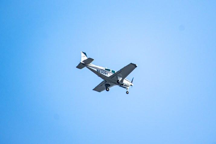 A plane flies overhead in a cloudless sky.