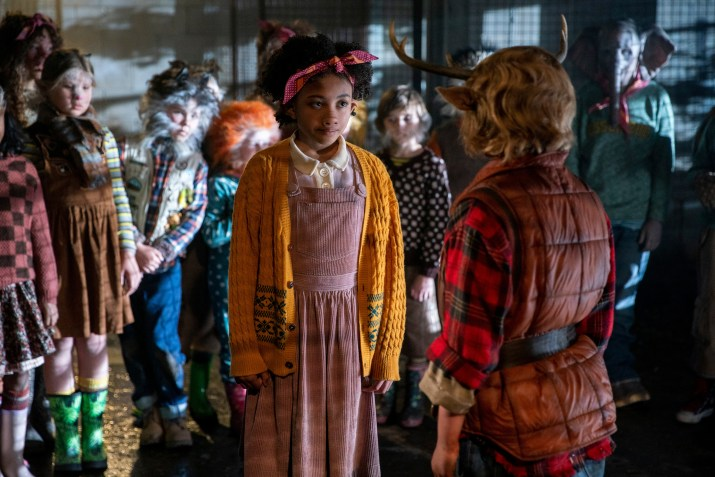 A girl with the nose of a pig stands in front of a group of children with various animal body parts. She faces another child with horns growing out of his head.
