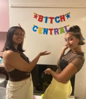 """Two female college students gesture to a sign on the wall that says """"Bitch Central."""""""