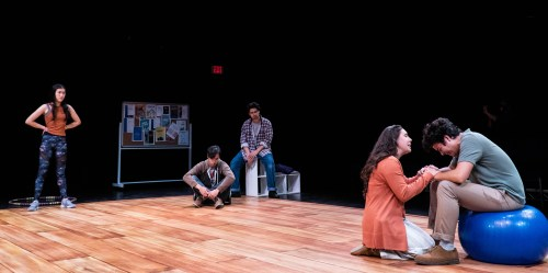 Five student actors, faces painted with emotions of angst and despair, sit in a circle.