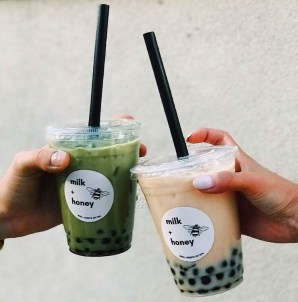 Two boba drinks are held.
