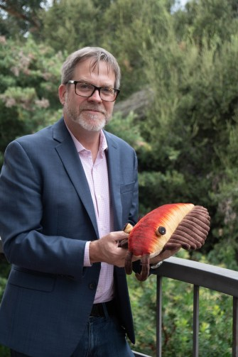 Bob Gaines poses with a model of the fossil.