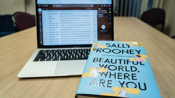 Sally Rooney's book in front of a laptop displaying a series of emails.