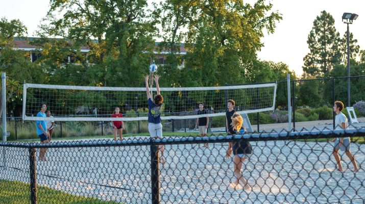 Students play volleyball on an outdoor beach volleyball court
