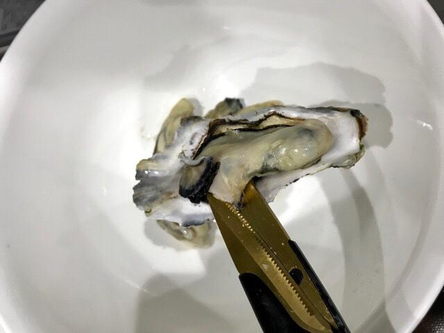 牡蠣の貝柱をハサミで切るところ